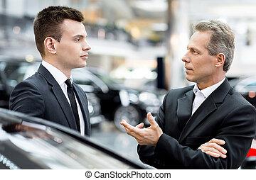 discutere, automobile, features., due persone, in, formalwear, parlando, altro, e, gesturing, mentre, standing, a, il, concessionario