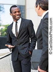 discutere, business., due, allegro, uomini affari, parlare, e, gesturing, mentre, standing, fuori