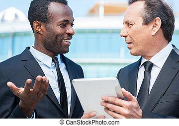 discutere, business., due, allegro, uomini affari, parlare, fuori, mentre, uno, di, loro, presa a terra, tavoletta digitale