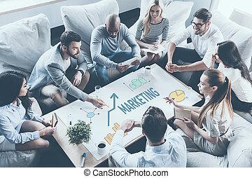 discutir, estratégia, junto., vista superior, de, pessoas negócio, discutir, algo, enquanto, sentar-se torno mesa, junto, e, apontar, grande, papel, com, gráficos, e, gráficos
