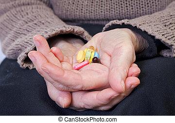 Close up of an elderly hand holding pills