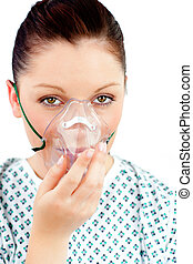 Diseased young woman with an oxygen mask looking at the...