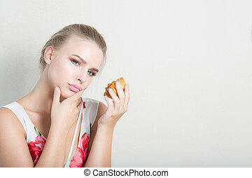 Disgruntled dieting blonde woman holding delicious dessert with cream. Space for text