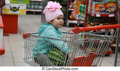 Disgruntled little girl in the supermarket is sitting in a cart for food. The child is upset and crying