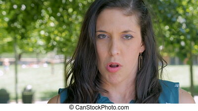 Disgusted unhappy woman in early 30s expressing her dissatisfaction outside at a park