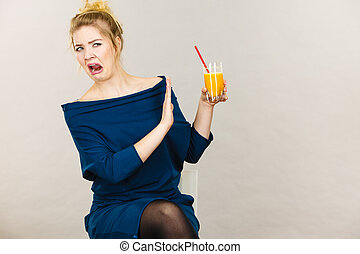 Disgusted woman holding orange juice - Disgusted blonde...