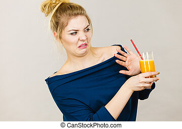 Disgusted woman holding orange juice