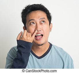 Asian man picking nose