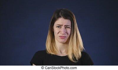 disgusting emotion. girl on dark background