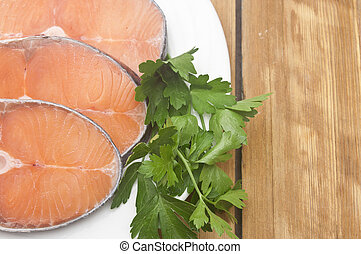 dish for baking with slices of salmon over wooden table