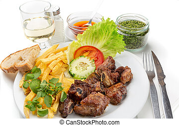 Dish for lunch of fried pork ribs, potatoes and salad. Portuguese dish.