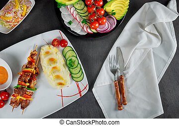 Dish of mashed potatoes, cherry tomatoes, cucumber and creamy sauce. Grilled skewers in the restaurant