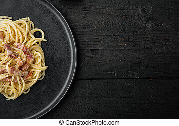 Dish of Spaghetti Carbonara, modern italian recipe of pasta with guanciale, egg ad pecorino romano cheese, on black wooden background, top view flat lay, with copy space for text