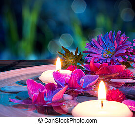 dish spa with 2 floating candles, orchid on mat