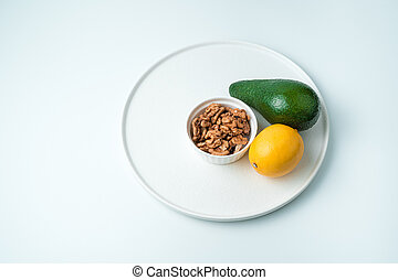 Dish with avocado, lemon and walnuts in a plate on a white background.