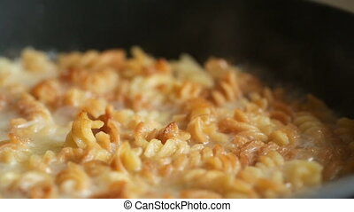 Dish with macaroni in a pan boils.