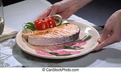 Dish with salmon put on the table. Slow motion