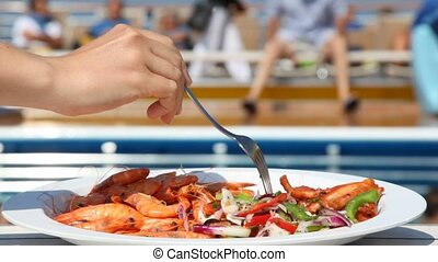 dish with shrimps and salad on table in front of pool