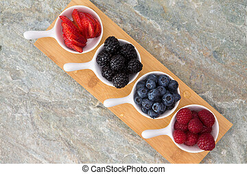 Dishes of fresh berries arranged diagonally on a small...