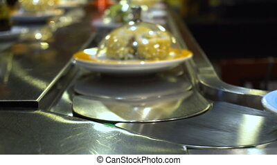 Dishes of Sushi and Sashimi rolling on conveyer belt - A lot...