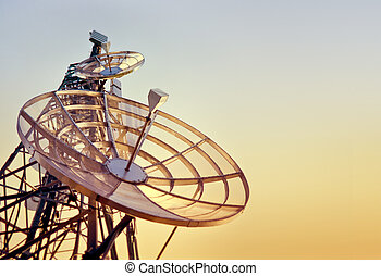 dishes on a telecommunications tower at the sunset
