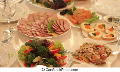Dishes with an appetizing cold snack on the festive table in...