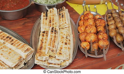 Dishes with pita, grilled meat and potatoes on skewers....