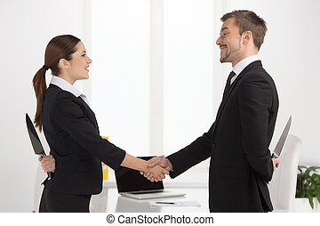Dishonest partnership. Two young business people shaking...