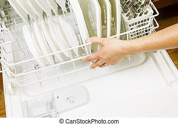 Dishwasher ready for use - Horizontal photo of female hand ...
