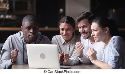 Multi racial group of diverse friends sit at table in bar look at pc screen feels disillusioned with game football match fans wait for victory after showing reaction face expressions of disappointment..