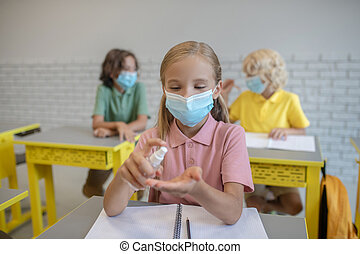 Disinfection. Fair-haired girl in a mask spraying sanitizer on her hands