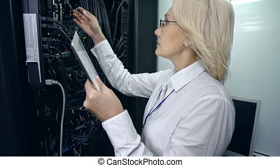 Tilt up of woman in supercomputer center copying data from rigid drive to her digital tablet device