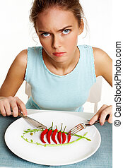 Dislike - Portrait of frowning girl with fork and knife in ...