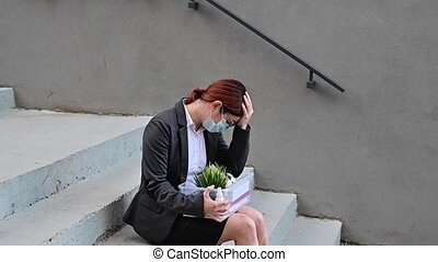 Dismissed woman with a box of personal belongings sits on the stairs on the outside. Female employee in medical mask fired due to financial crisis in coronovirus. Unemployment