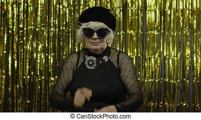 Displeased annoyed senior old woman showing stupid gesture, accusing crazy cuckoo mind, blaming insane idea, senseless dumb talk. Elderly stylish lady grandma on golden background. 6k slow motion