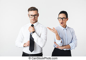 Displeased business woman looking at her colleague man isolated over white wall background.