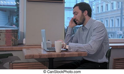 displeased businessman talking on the phone in cafe