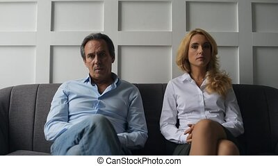 Displeased couple talking with psychologist