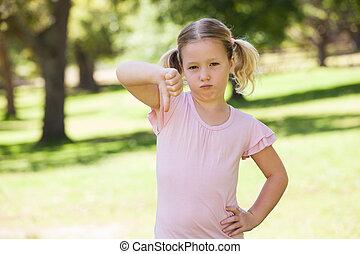 Displeased girl gesturing thumbs down at park
