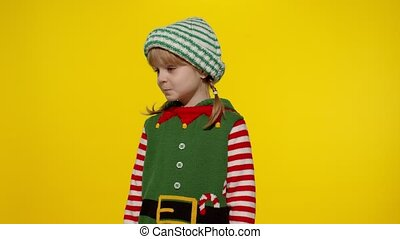Displeased little blonde kid teen teenager girl in Christmas elf Santa helper costume isolated on yellow studio background. Child looking unhappily angry, sad at camera. Negative emotions and reaction