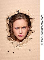 Displeased girl peeping through hole in paper