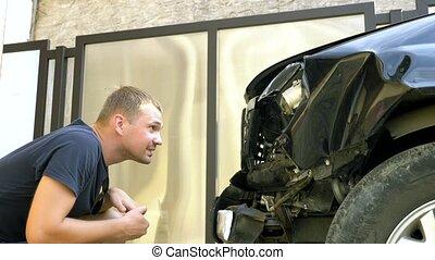 Displeased man sitting near a car with a broken bumper. car...