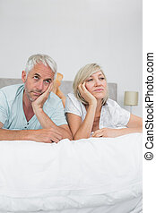 Displeased mature man and woman lying in bed - Closeup of...