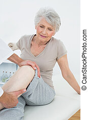 Displeased senior woman getting her leg examined at the...