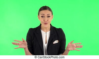 Displeased woman indignantly talking to someone, looking at the camera. Girl with dark hair wearing a black business suit at green screen at studio.