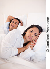Displeased woman lying next to snoring boyfriend -...