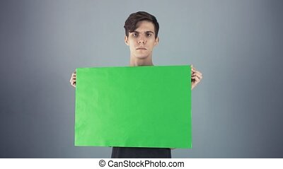 Displeased Young man in black shirt holding green key sheet poster gray background
