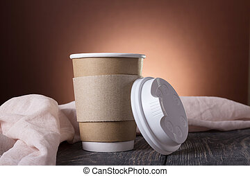 Cup-thermos with lid for coffee to take away, on background of wooden table