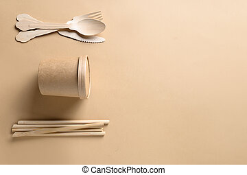 Disposable paper cups, individual wooden spoons, forks, bamboo straws on beige.