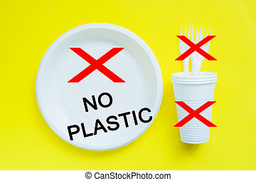 Disposable plastic tableware on bright yellow background with copy space. concept of protest and the words No Plastic